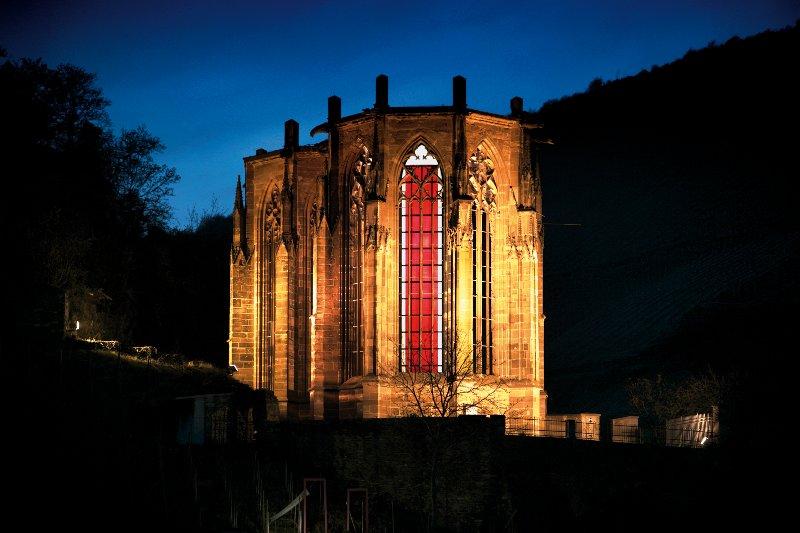 """Glasinstallation von Karl-Martin Hartmann in der Wernerkapelle Bacharach. Auf sechzehn der strahlend roten 53 Scheiben ist der Beginn von Heinrich Heines Erzählung """"Der Rabbi von Bacherach"""" aufgedruckt."""